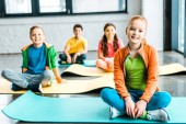 Children sitting on fitness mats and looking at camera with smile