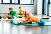Group of kids stretching on colorful fitness mats