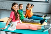 Smiling stylish kids sitting on fitness mats