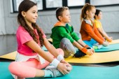 Smiling kids doing gymnastic exercises on fitness mats