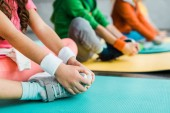 Fotografie Cropped view of kids stretching on fitness mats