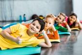 Veselé děti ležící na fitness rohože v tělocvičně