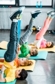 Fotografie Kids doing candlestick exercise on mats in gym