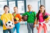 Bezstarostné děti pózuje s míčky v tělocvičně