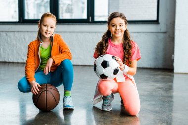 Excited kids posing with balls in gym stock vector