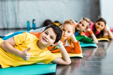 Cheerful kids lying on fitness mats in gym stock vector