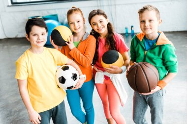 Excited children in sportswear posing with balls stock vector