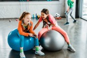 Photo Laughing kids with smartphone sitting on fitness balls