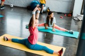 Happy kids smiling while doing twine on fitness mats
