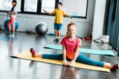 Excited kid doing twine on yellow fitness mat