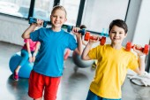 Cheerful boys laughing while training with dumbbells