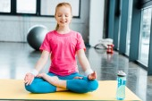 Fotografie Ginger dítě cvičí jógu a sedí v lotosu představují se zavřenýma očima