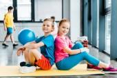 Rozkošné děti sedí zády k sobě na fitness mat