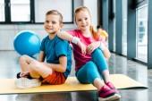 Preteen Přátelé sedící na fitness mat v tělocvičně