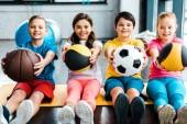 Veselé děti sedí na fitness podložka s míčky