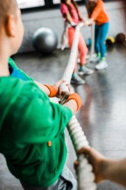 Children playing tug of war in gym