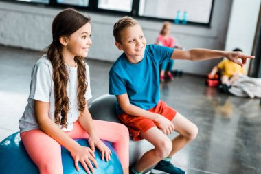 Preteen kids chatting while sitting on fitness balls