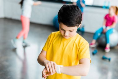 Boy in yellow t-shirt looking at smartwatch