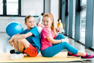 Two kids sitting  back to back on fitness mat