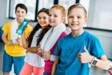 Smiling kids with towels posing after training in gym
