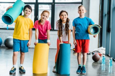 Group of kids posing in gym with fitness mats