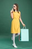 Fotografie elegantní žena ve žlutých šatech a sluneční brýle s nákupní tašky ukázal rukou na zeleném pozadí