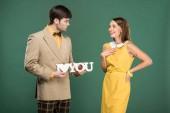Fotografia uomo che presenta il segno decorativo ti amo a bella donna sorpresa in vestiti dellannata isolato su verde