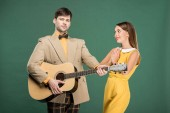Photo handsome man in vintage clothes playing acoustic guitar while beautiful woman doing please gesture isolated on green