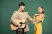 Photo handsome man in vintage clothes playing acoustic guitar for beautiful smiling woman isolated on green