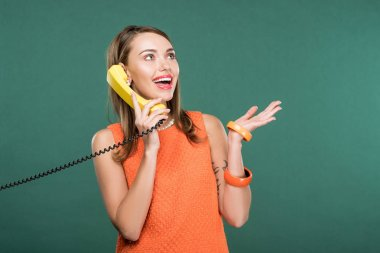 beautiful happy woman talking on retro telephone isolated on green