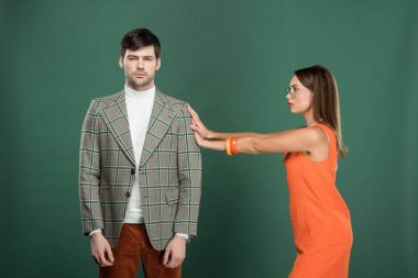 beautiful woman pushing handsome man in vintage clothes isolated on green