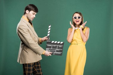 Handsome man in vintage clothes holding film clapperboard while happy woman gesturing with hands isolated on green stock vector