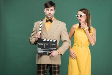 Handsome man in vintage clothes holding film clapperboard while woman covering mouth and pouting lips isolated on green stock vector