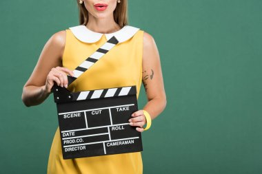 cropped view of stylish woman in yellow dress holding film clapperboard isolated on green with copy space