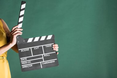 cropped view of woman holding film clapperboard isolated on green with copy space