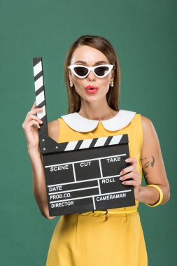 Beautiful stylish woman in yellow dress and sunglasses holding film clapperboard isolated on green stock vector