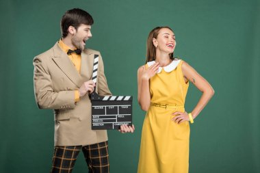 Handsome man in vintage clothes holding film clapperboard while beautiful woman posing isolated on green stock vector