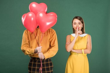 beautiful woman doing silent gesture while man covering face with heart shaped balloons isolated on green