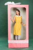 beautiful stylish woman in yellow dress posing in decorative pink box with bow on green background