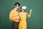 aufgeregt paar in Vintage-Kleidung und virtual-Reality-Kopfhörer isoliert auf grün