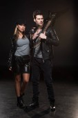 Photo beautiful fashionable couple in leather jackets posing with electric guitar on black background
