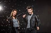 Schönes Paar in Lederjacken mit Rock und Daumen nach oben Zeichen beim Jubel mit fallendem Konfetti auf schwarzem Hintergrund