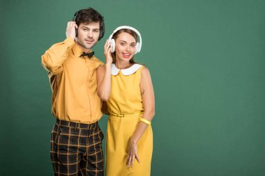 beautiful happy couple in vintage clothes with headphones isolated on green