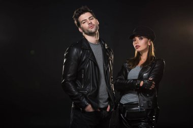 beautiful couple in leather jackets looking at camera and posing on black background