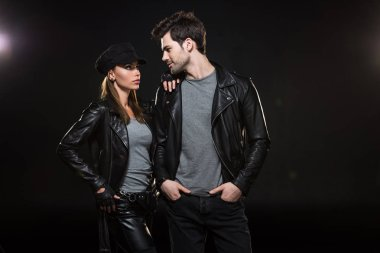 beautiful fashionable couple in leather jackets posing on black background