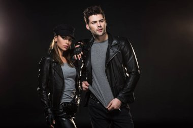 beautiful stylish couple in leather jackets posing on black background