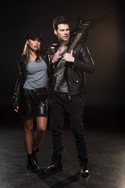 beautiful fashionable couple in leather jackets posing with electric guitar on black background