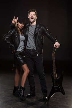 beautiful couple in leather jackets posing with electric guitar on black background