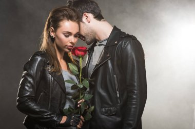 beautiful couple in leather jackets posing with red rose on smoky background