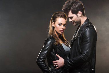 beautiful couple in leather jackets embracing on dark background with copy space